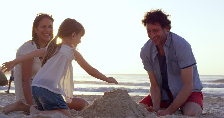 Happy family playing on the beach building sand castle at sunset on vacation slow motion RED DRAGON