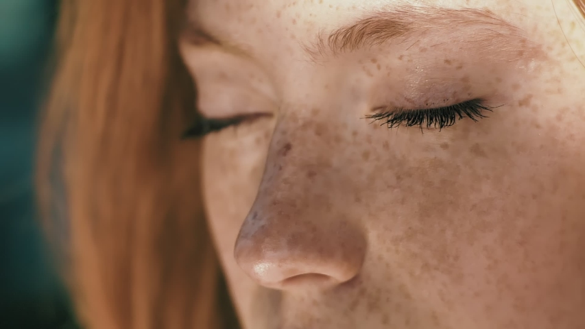 Beautiful woman's eyes opening while looking at Camera, having long nice Eyelashes. Attractive girl with nice Freckles on her Beautiful Face. Red haired woman with Charming Appearance Royalty-Free Stock Footage #1046787226
