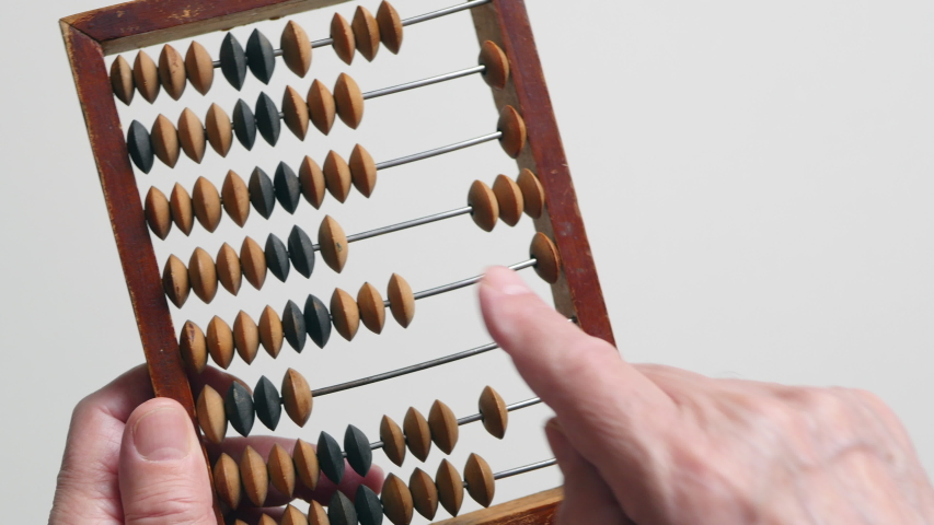 A Elderly Man Is Holding And Moves Wooden Knuckles On A Outdated Vintage Wooden Abacus On A White Background, Close-up On The Left Side.