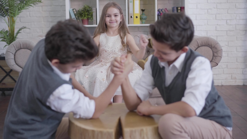 Portrait of joyful Caucasian little girl cheering on couch as blurred twins competing in armwrestling at the foreground. Sister having fun with brothers indoors. Family, joy, leisure, lifestyle.
