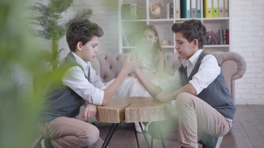 Two identical twin brothers competing in armwrestling and talking as their little sister cheering at the background. Happy children enjoying free time at home. Shooting from behind house plant.