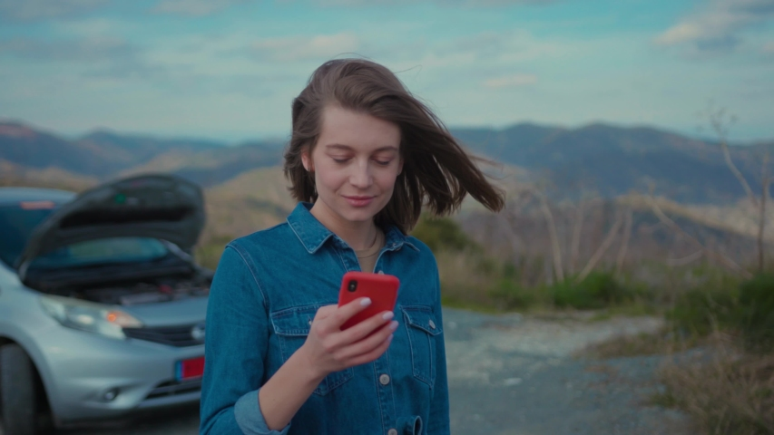 Young upset woman standing at broken car searching for repair service on smartphone worrying in stress. Car accident. Car trouble.