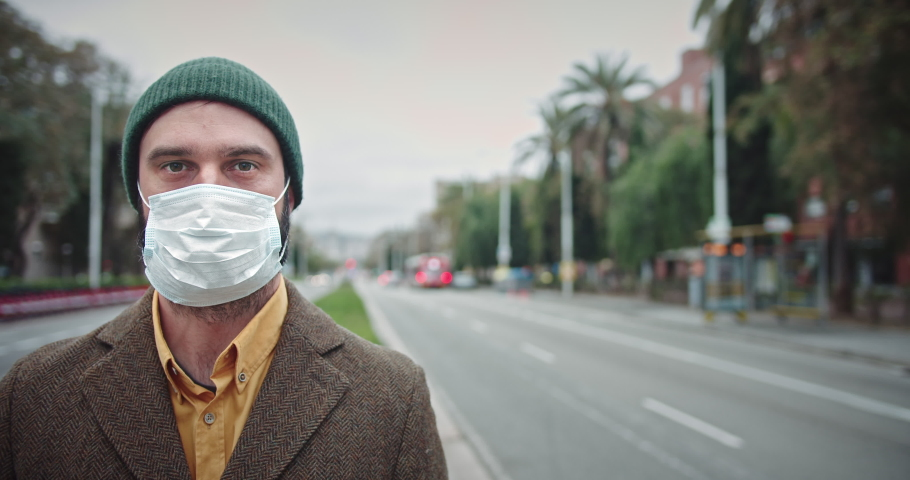Pandemic N1H1 coronavirus protection. Young hipster tourist man wearing protective mask on traffic street background.Concept of health and safety life, N1H1 coronavirus, virus protection.Cinematic | Shutterstock HD Video #1046801644