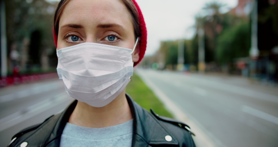 Pandemic Covid-19 coronavirus protection. Portrait of a european hipster woman wearing protective mask street.Concept of health and safety life, N1H1 coronavirus, virus protection.Cinematic Closeup | Shutterstock HD Video #1046801650
