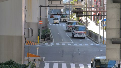 Osaka Japan 2019 November 06: Trucks passing through the highway road in Osaka Japan with the street signage on the side