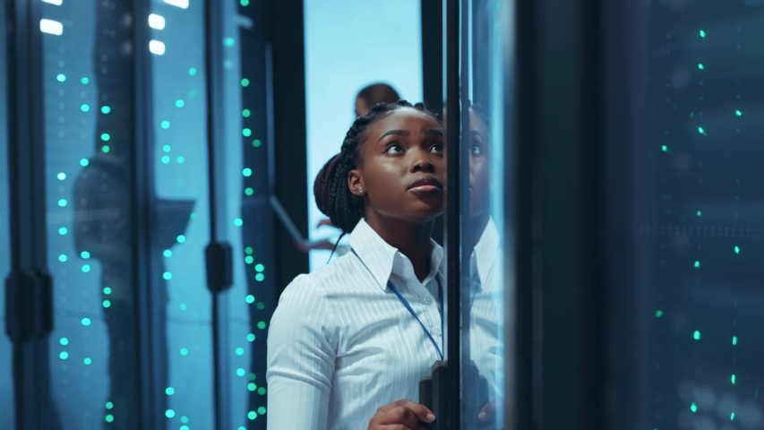African american woman engineer working in business team of data center inspecting open server racks and typing data on tablet. People and technology. Royalty-Free Stock Footage #1046828476