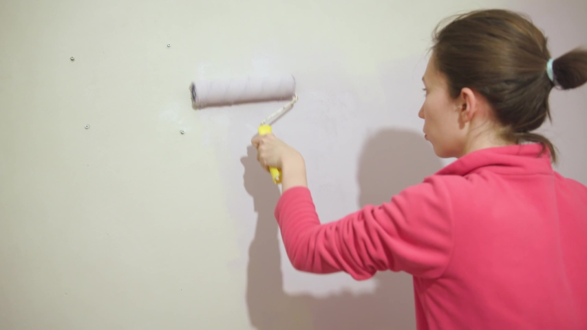 Happy beautiful young woman doing wall painting. | Shutterstock HD Video #1046831878