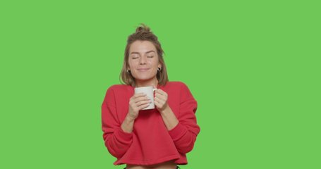 Pretty smiling girl drinking coffee isolated on green screen background. Young white woman with hot drink smiling on Chroma key. 4k raw video footage slow motion