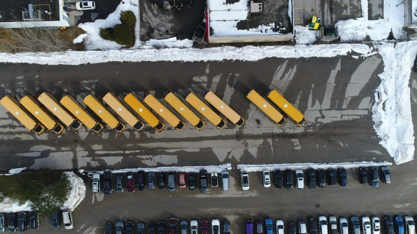 Descending Aerial Over Tops of Yellow Schoolbuses in Highschool Parking Lot in Winter With Snow