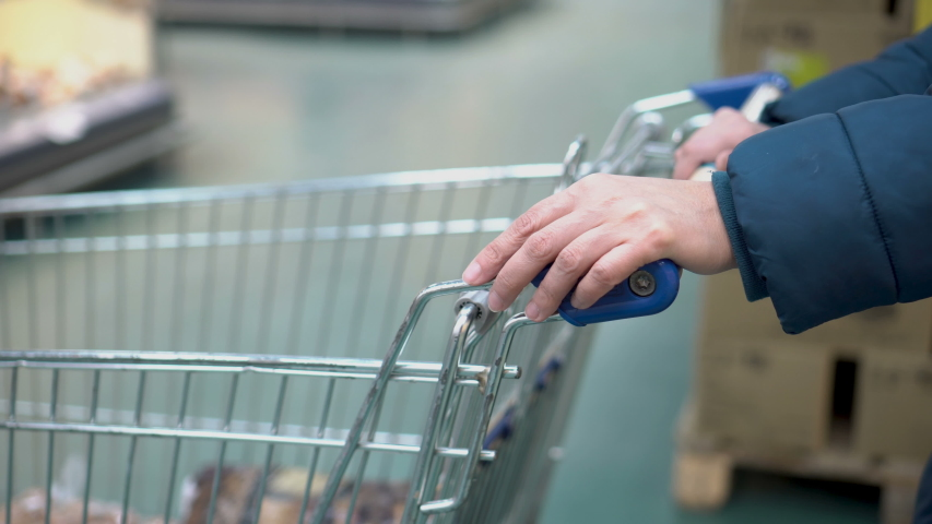 A woman with a shopping cart is standing in line at the store's checkout and nervously taps her finger on the cart. Shopping at the supermarket. Faceless. Concept. 4K.