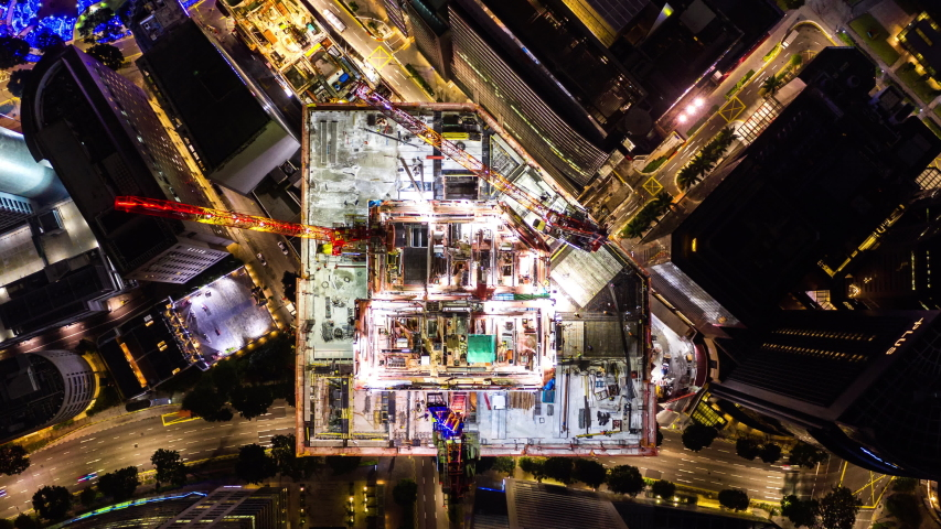 4K hyperlapse time-lapse of under construction site, crane, and car traffic transportation at night in city downtown. Drone aerial top view. Industrial business or civil engineering technology concept