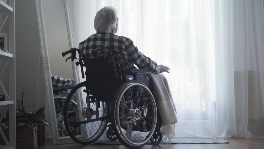 Back view of old Caucasian man sitting in wheelchair in front of big window closed with curtain and thinking. Lonely elderly man spending day alone at home. Oldness, retirement, disabled people.