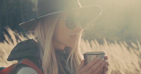 Close-up Woman hiking backpacker traveler drinking hot tea and relaxing in the fall forest on sunny autumn day. Beautiful mountain landscape view. 4K slow motion video.