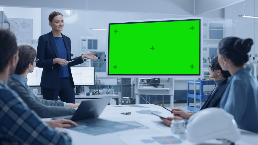 Modern Industrial Factory Meeting: Confident Female Engineer Uses Interactive Green Mock-up Screen Whiteboard, Makes Report to a Group of Engineers, Managers Royalty-Free Stock Footage #1046904922