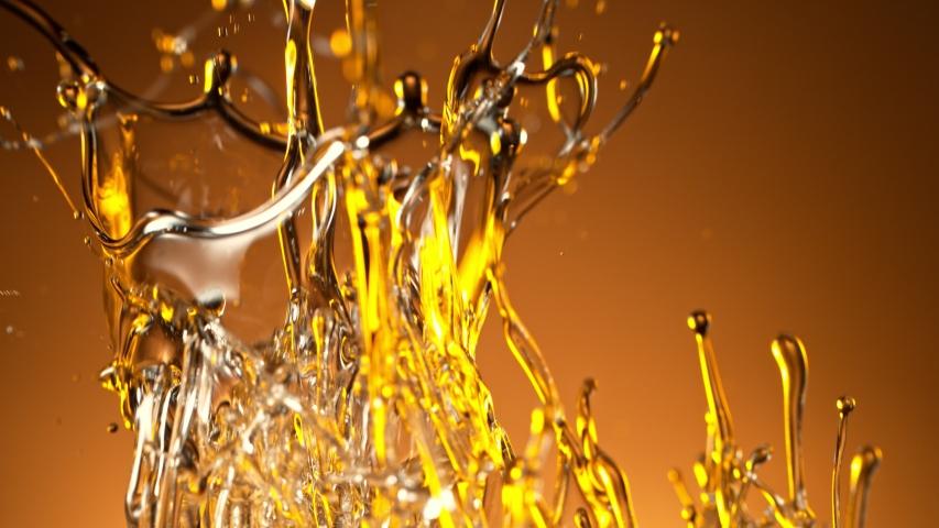Super Slow Motion Shot of Splashing Oil on Golden Background at 1000fps.