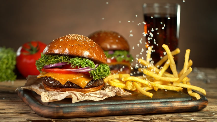 Super Slow Motion Shot of Fast Food Concept. Falling French Fries on Wooden Cutting Board next to the Fresh Hamburger at 1000fps.