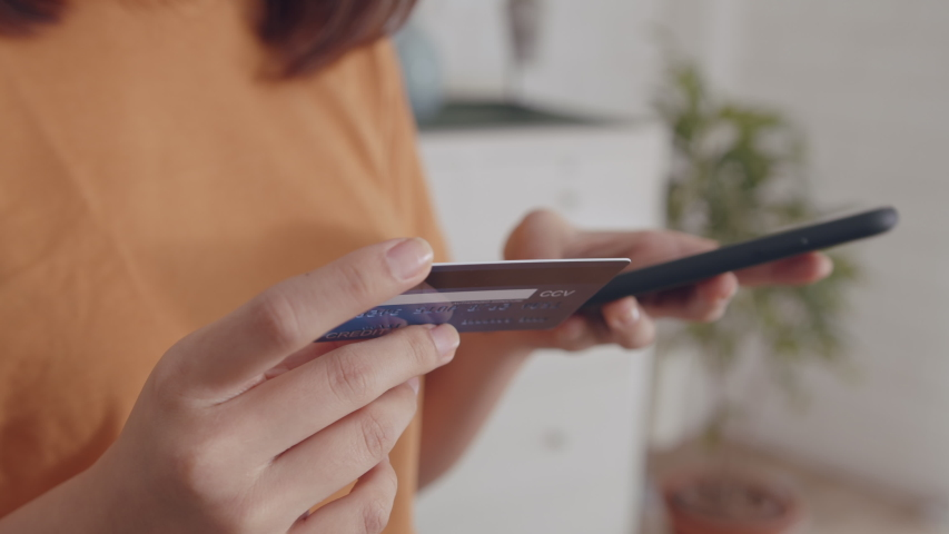 Young Asian Woman hand holding credit card using a digital mobile device and Buying online, internet shopping. Close-up Asian Female hand typing bank card number into a smartphone.Lifestyle Concept. Royalty-Free Stock Footage #1046915872