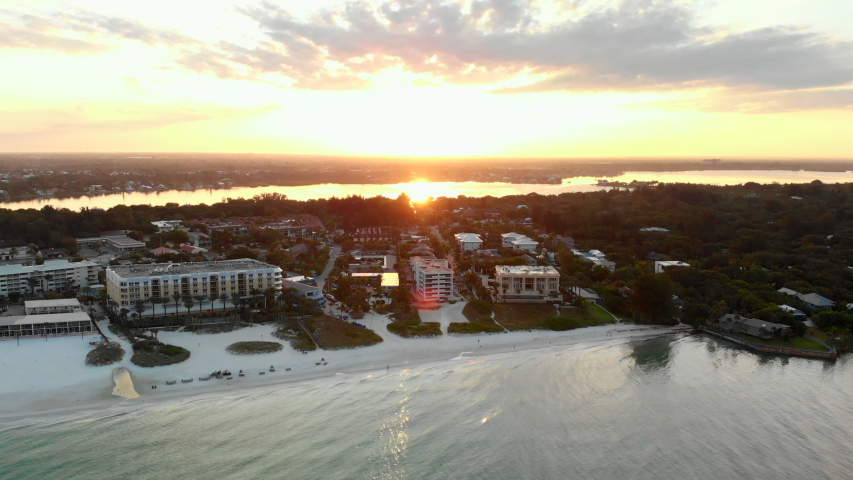 Wide aerial, beachfront vacation town in soft light, sunset in background