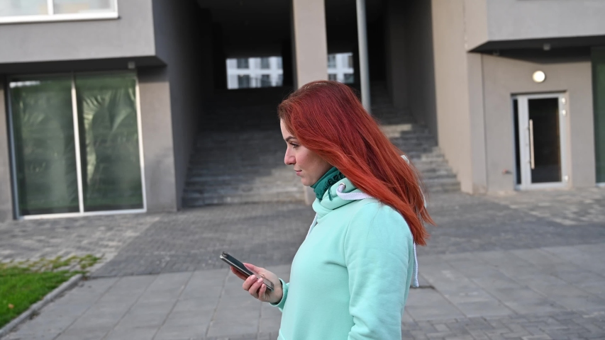 A beautiful redhead woman in a mint sweatshirt is walking the street and talking on the phone. Happy girl takes a selfie and chatting on a smartphone.   Shutterstock HD Video #1046922592