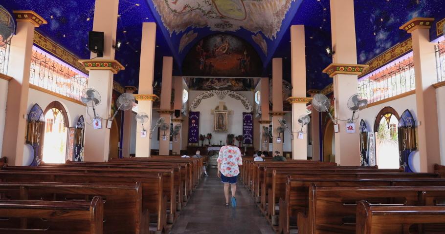 HUATULCO, MEXICO - 10 APR 2019: Huatulco city Mexico La Crucecita Church woman walks away. Christianity main religion. Tourist development in Mexico. Pacific coast in state of Oaxaca. Tourism industry