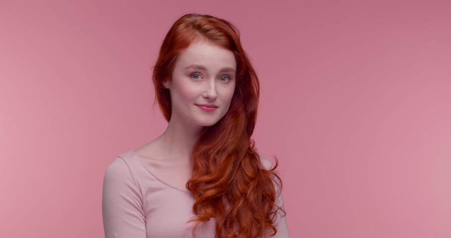 Natural Beauty red-haired Girl touching her perfect wavy Hair and smiling. Portrait of Amazing young Girl looking cute to the Camera, wearing pink Top, nude Makeup. Healthy Skin and Hair. Care. Girl. | Shutterstock HD Video #1046928586