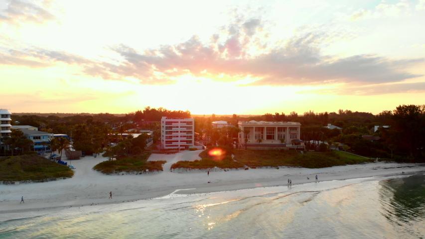 Aerial pullback, beachfront homes on calm beach, spectacular sunset on horizon