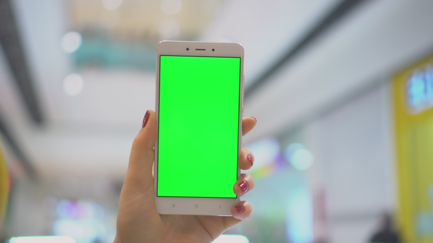 Woman focused on her smartphone while displaying a green screen. Concentrated at the screen of her device. Chroma key slide shot | Shutterstock HD Video #1046941000