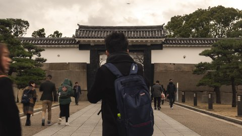 Osaka, Japan, - December 29 2019 : Time lapse of traveller visiting walk in and out of Osaka castle's gate