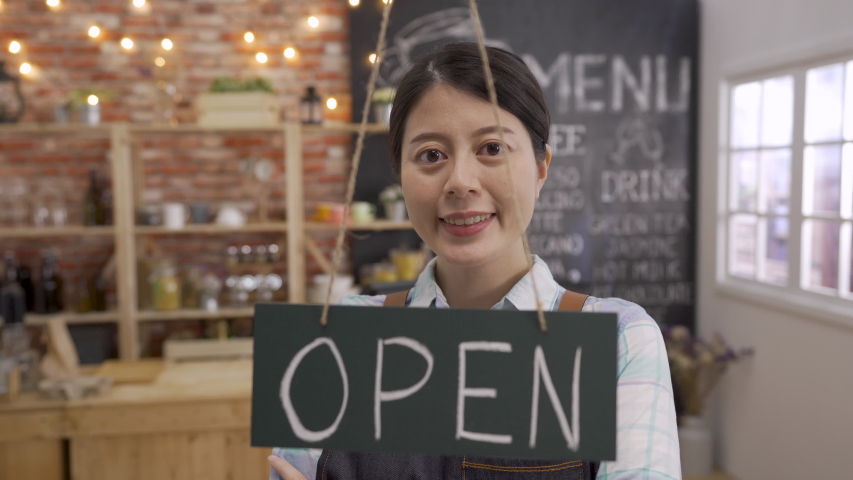 Business cafe bar sign board hang on door and show open with cafe and restaurant blur bokeh background. young asian female coffee shop owner waitress walking to door welcome face camera smile lovely | Shutterstock HD Video #1046943895