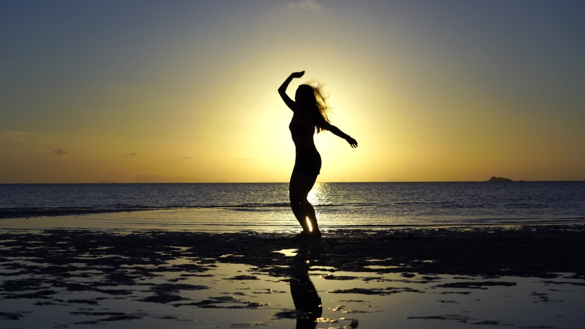Happy young woman dancing on a tropical beach during sunset. Dance of caucasian girl near sea water #1046960011