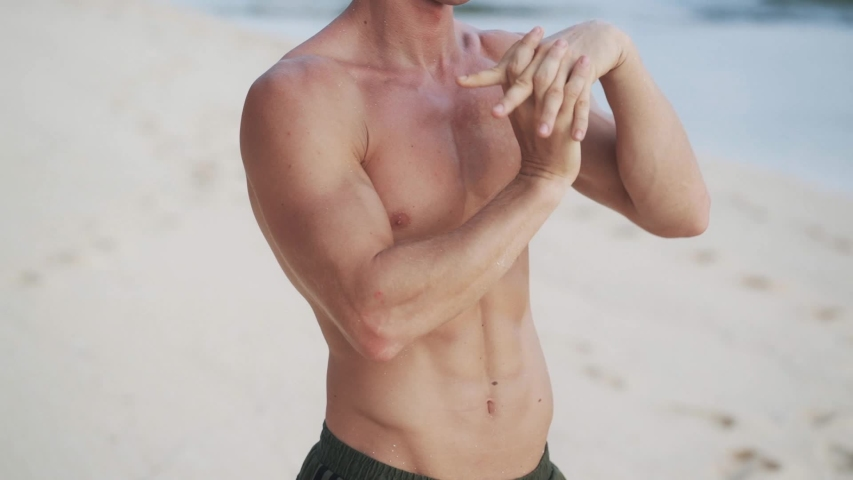 Man with muscular bare torso does warm-up stretching hands arms before yoga exercises on sand beach close view slow motion | Shutterstock HD Video #1046966482