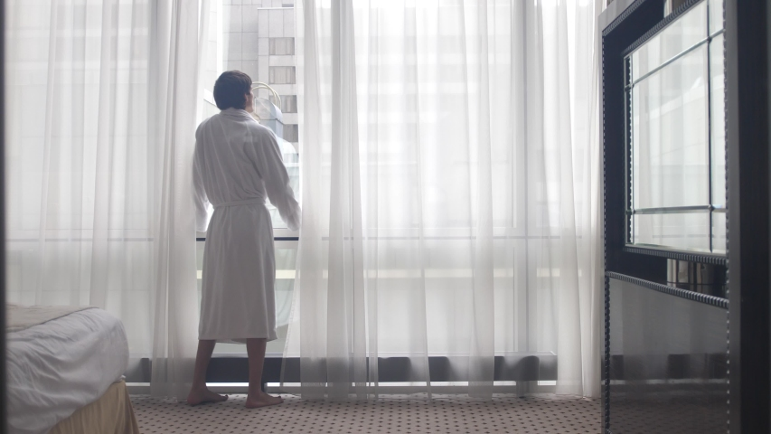 Young man wearing bathrobe drinking coffee by the window | Shutterstock HD Video #1046970241