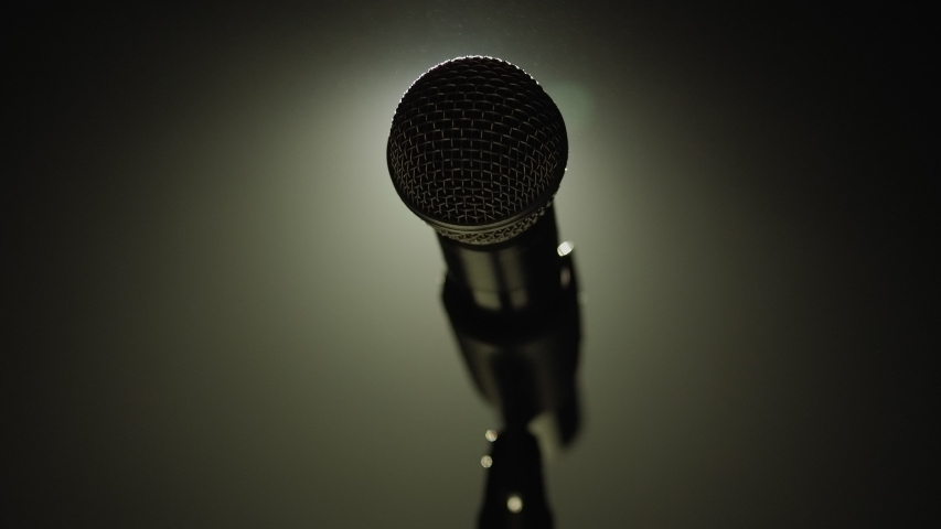 Close-up of microphone on stage against a black background with white lighting and smoke. The silhouette of the microphone in the dark. Music instrument concept. Royalty-Free Stock Footage #1046972356