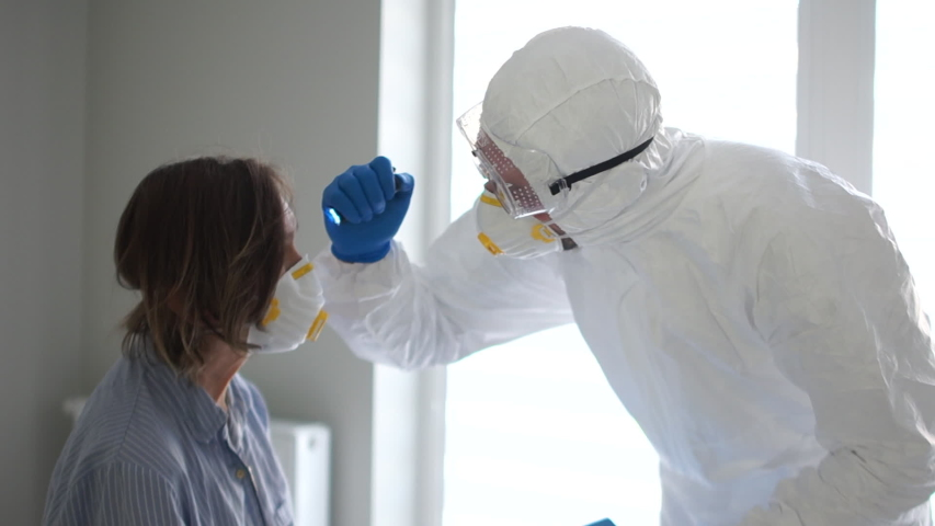 Doctor in a protective mask and glasses examines a woman with a flashlight. Pandemic threat, coronavirus threat. Covid19