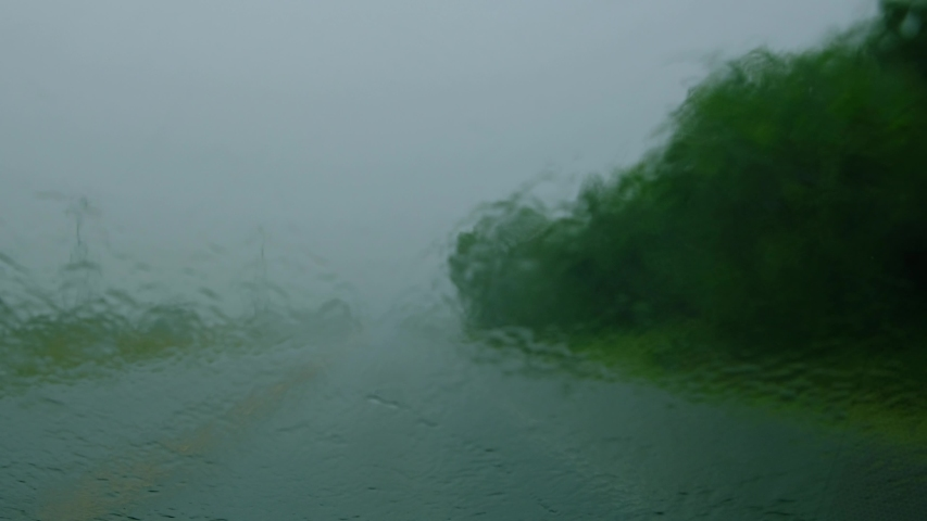 Car driving thru heavy rain storm with water on windshield making it hard and dangerous to drive. Incoming traffic have the lights turned on for safety. The wipers are turned on at high speed  | Shutterstock HD Video #1046979085