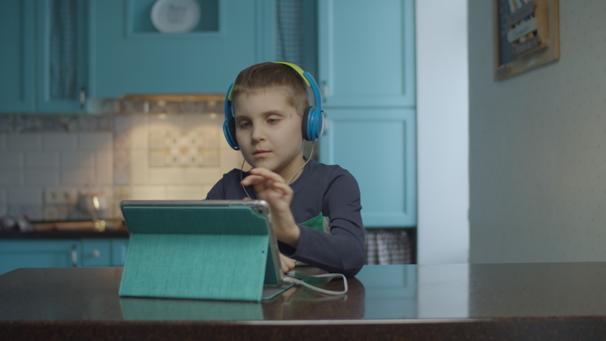 Autistic boy using tablet computer with headphones on the kitchen. Kid with autism looking around at home. Autism awareness