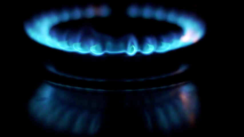 Gas is switching on, apearing blue flame. Gas stove on black background. Slowmo