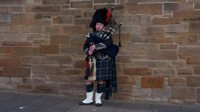 Bagpipe musician in the streets of Edinburgh - EDINBURGH, UNITED KINGDOM - JANUARY 10, 2020