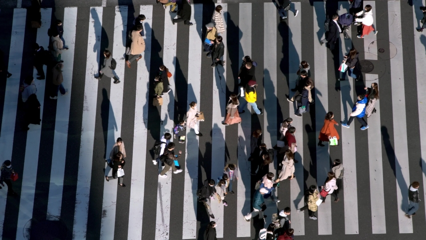 4K, Aerial view over a traffic cars and a crowd of pedestrian crossing street with a sunset light. Elevated view over an asian people walking in busiest road intersection. -Dan Royalty-Free Stock Footage #1047000202