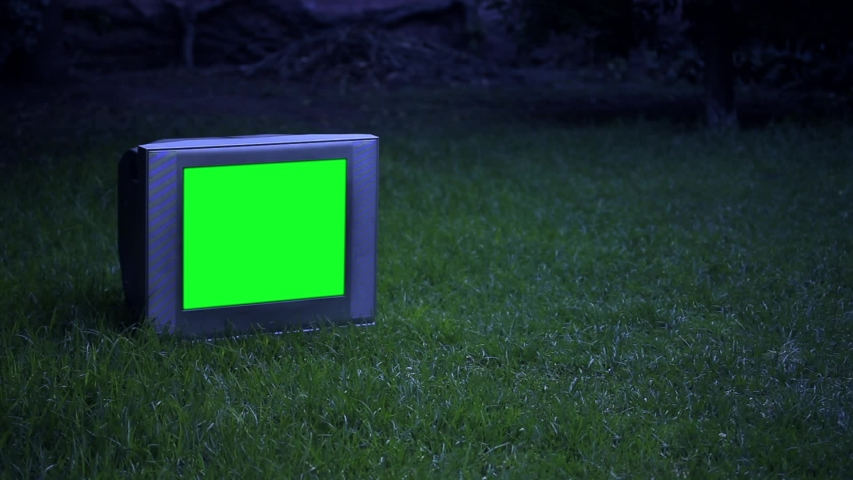 """Old TV with Green Screen over Green Grass at Night. Zoom In. You can Replace Green Screen with the Footage or Picture you Want with """"Keying"""" effect in After Effects (check out tutorials on YouTube). 