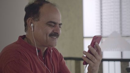 A happy old man using smartphone and earphones to chat with a wife over a video call in a long distance relationship. Smiling Grandpa talking with his son/ friend working abroad in indoor home setup.