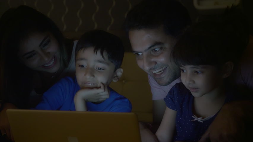A family of four members including parents and two young siblings are enjoying while using tablet or Laptop in the night. A happy family smiling while watching a movie or playing online video game.