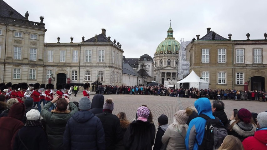 Copenhagen, Denmark - January 1, 2020: Amalienborg Palace is filled with tourists and residents to watch the royal guard change at noon on New Year's Day with the Marble Church in the background