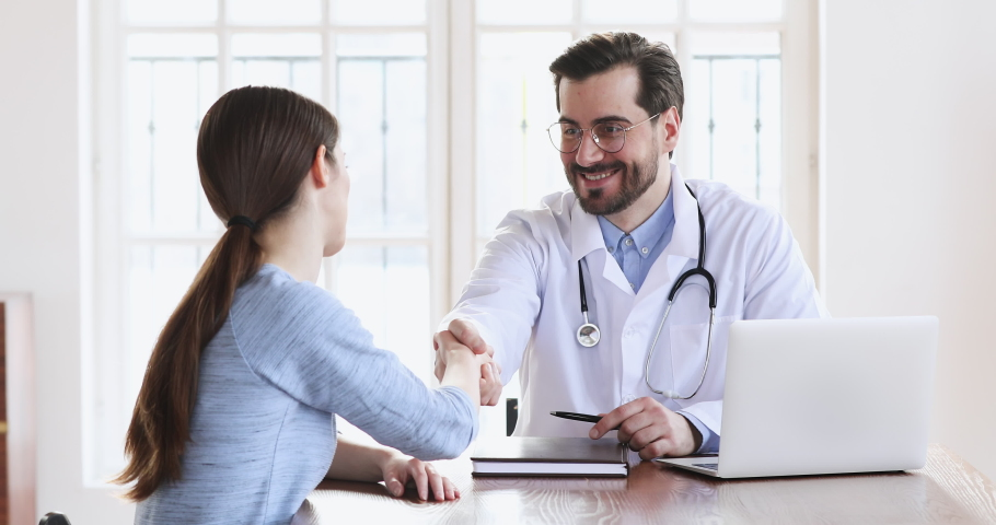 Smiling male professional doctor plastic surgeon handshakes female patient agree on surgery. Happy physician in white uniform shake hand of woman at medic checkup visit, medical service trust concept Royalty-Free Stock Footage #1047021430