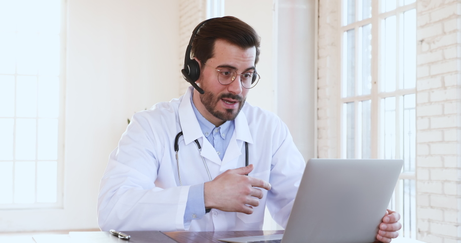 Professional male doctor in white medical coat and headset making conference call on laptop computer, consulting distance patient online in video chat, explain treatment by webcam concept