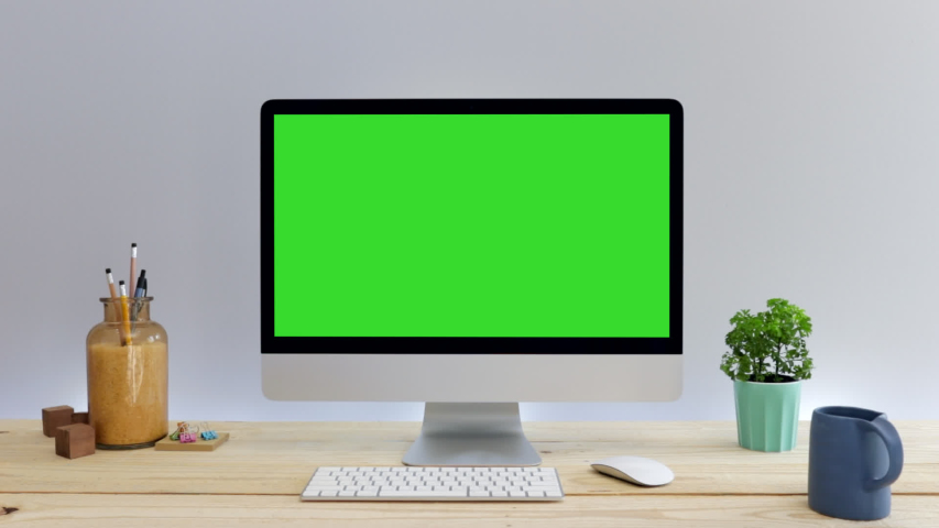 Computer desktop with mock-up green screen on wood table with grey background in office, Zoom shoulder view.   Shutterstock HD Video #1047028777