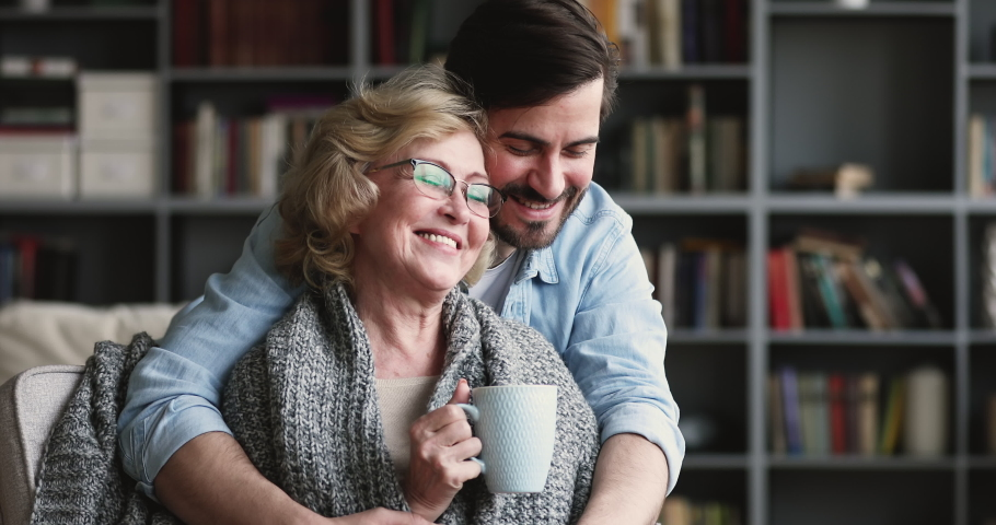 Happy loving adult grown son embrace old middle aged mother sit covered with warm blanket on chair drink tea on cozy weekend at home. Two 2 age generations hugging look at camera posing for portrait Royalty-Free Stock Footage #1047036829