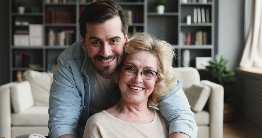Smiling 30s young adult man grown handsome son looking at camera hugging old mature 60s mom expressing love and care embracing cuddling on mothers day concept. 2 generations family closeup portrait