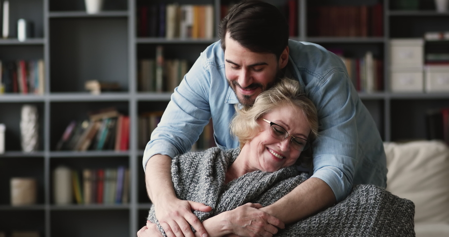 Caring affectionate young adult man grown son coming to mature middle aged mother sit on chair covering older parent with warm plaid blanket hugging relaxed senior mum showing care support at home #1047036841