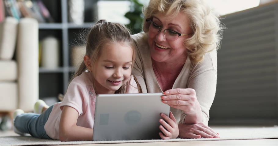 Old mature grandma nanny teaching cute small preschool granddaughter learning reading ebook on digital tablet. Two generation family grandparent and grandchild using pad device tech on floor at home